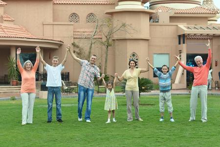 Familia feliz que se relaja en el centro turístico de vacaciones con las manos arriba Foto de archivo