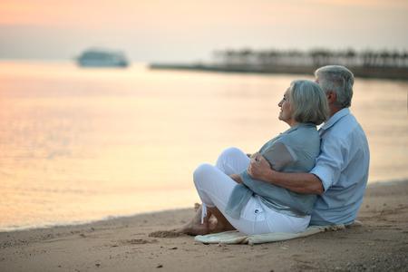 Portret van een senior paar op zee bij zonsondergang