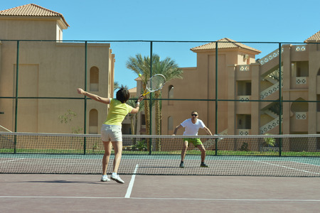 near: Tennis players standing near net on court