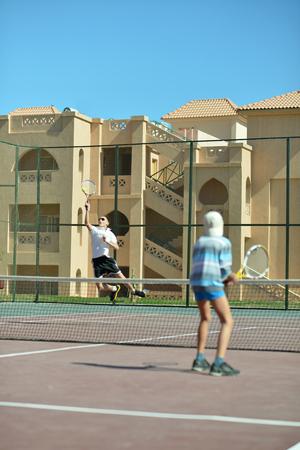 hermanos jugando: Dos hermanos activos que juegan en la pista de tenis