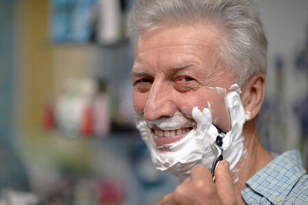 beautycare: Portrait of a senior man shaving in bath