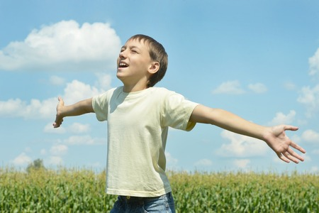 enjoys: Happy boy in field enjoys nature against the sky