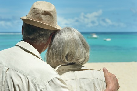 Beautiful happy elderly couple rest at tropical resort,back view