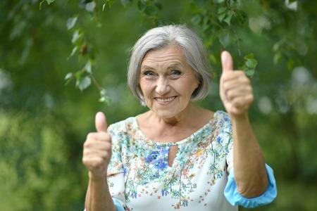 Senior vrouw zien thumbs up in het park Stockfoto