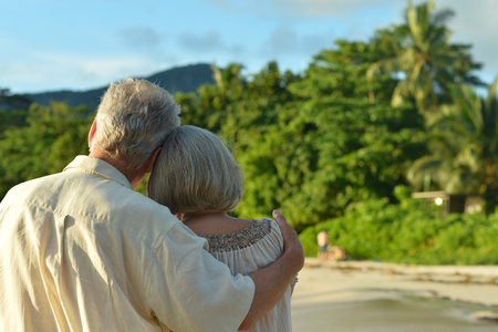 seniors couple: Beautiful happy elderly couple rest at tropical resort,back view