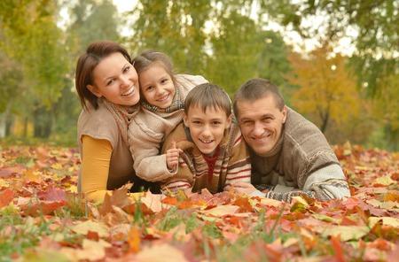 familias felices: Familia sonriente feliz que se relaja en parque del otoño Foto de archivo