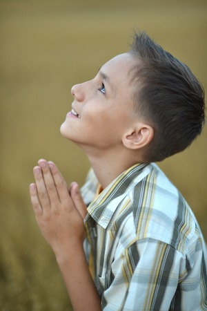 Portrait of a young  praying boy  in field