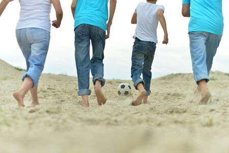 guy portrait: Big Family playing football on a beach in summer day
