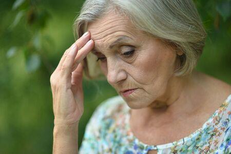 personas pensando: Niza mujer mayor triste en el fondo de la primavera