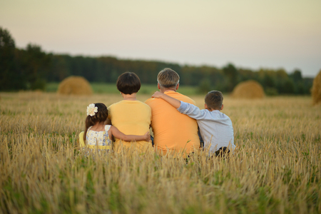 woman back view: Happy family in wheat field in sunny day,back view Stock Photo