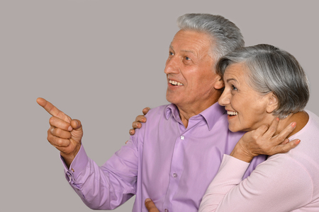 Portrait of happy old couple on background,man pointing by his finger Stock Photo - 44011512