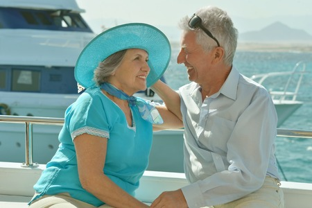 Happy elderly couple have a ride in a boat on sea Stock Photo