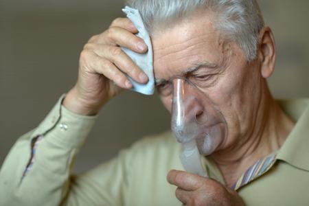 gripe: Retrato de hombre de edad avanzada con la inhalación de la gripe Foto de archivo