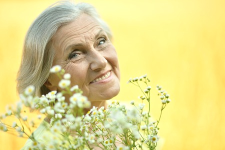 the caucasian beauty: Portrait of a senior woman with flowers in field