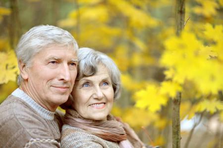 senior adults: Portrait of a happy senior couple in autumn park