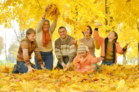 Friendly family on a walk during the fall of the leaves in the park