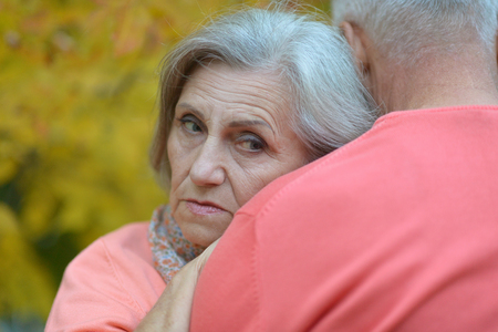sad old woman: Portrait of a sad senior couple in autumn park