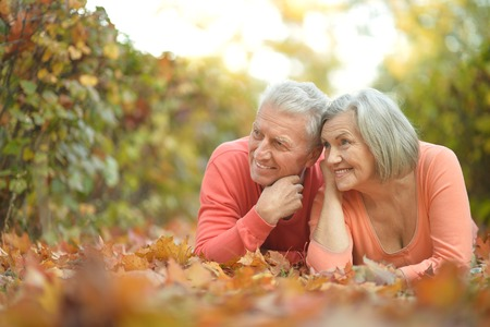 lying on leaves: Mature couple lying on leaves in the autumn park Stock Photo