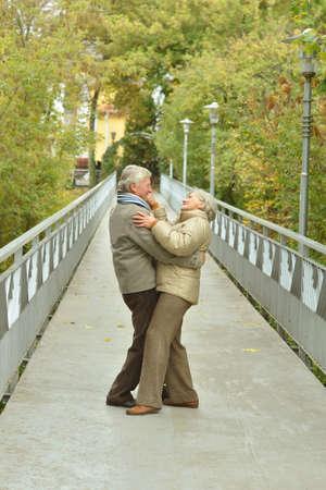 dult: Happy senior couple rest in autumn park