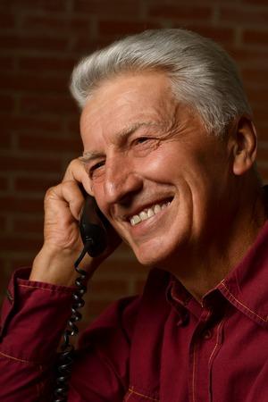elderly: Elder man in a shirt on a brick background Stock Photo