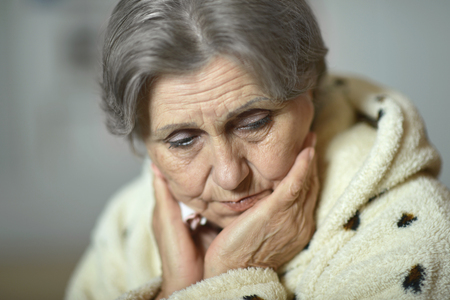 sick person: Portrait of an ill senior woman at home
