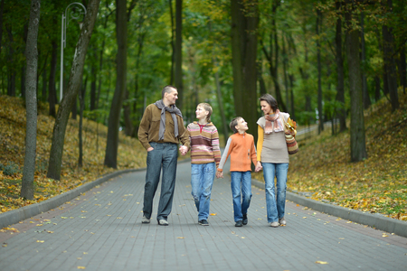 mom and dad: Portrait of happy family relaxing in autumn park Stock Photo
