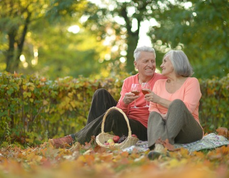 Senior couple resting at autumn park with picnic food