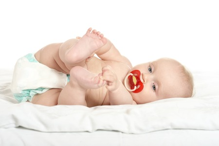 female children: Adorable baby girl on blanket with nipple on a white background