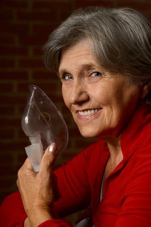 inhaler: Older sick woman with inhaler in red