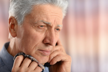 old man standing: Sick old man standing on blue background calling doctor Stock Photo