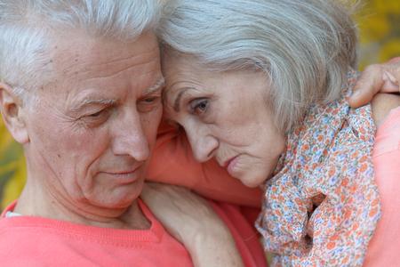 lamentable: Close-up portrait of a sad elder couple in autumn park
