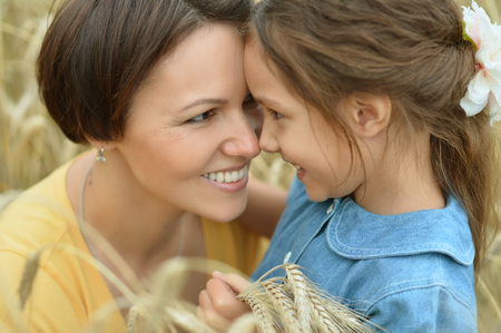 mother care: Mother and daughter at summer rye field