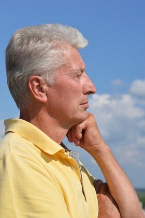 hombre solitario: Retrato de un hombre mayor que piensa en algo al aire libre