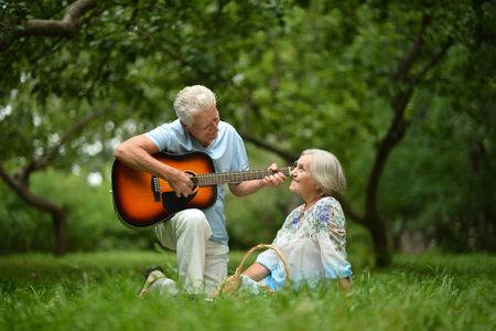 Loving mature couple with guitar   in summer park