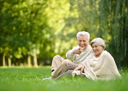jubilados: Pareja de ancianos sentados juntos en el otoño de parque hierba