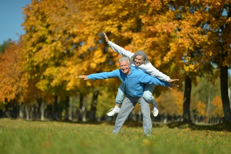 mature people: Portrait of a happy senior couple resting at autumn park Stock Photo