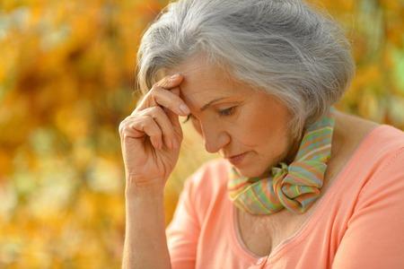 one senior adult woman: Happy beautiful senior woman in the autumn park Stock Photo