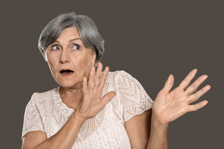 agape: Portrait of a scared elderly woman on grey background