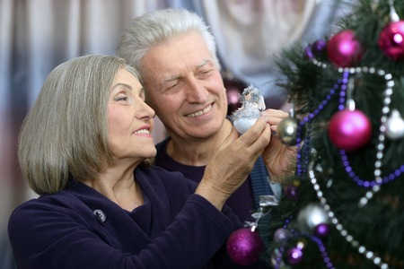 home decorated: Happy beautiful elderly couple celebrating new year at home,decorated christmas tree Stock Photo
