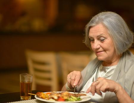 카페에서 아침 식사를 먹는 행복 수석 여자의 초상화 스톡 콘텐츠