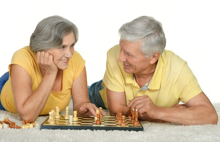 pawn adult: Happy elderly couple playing chess at home Stock Photo