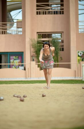 petanca: Beautiful woman playing Boules game  on tropical resort Foto de archivo