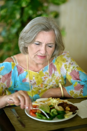 senior adults: Senior woman eating breakfast at a cafe Stock Photo