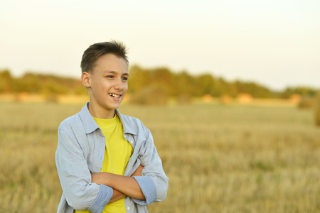 enjoys: Portrait of a happy boy in field enjoys nature Stock Photo