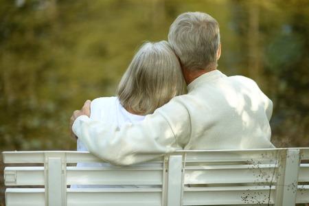 Amusing senior couple sitting on bench in park