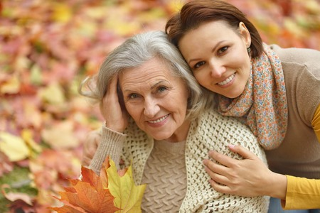 adult care: Mother and her nice daughter in autumn park Stock Photo
