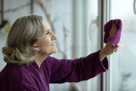 Portrait of a senior woman cleaning window at home