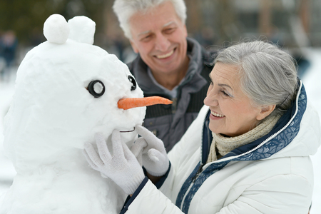 couple winter: Happy senior couple with snowman in winter outdoors Stock Photo