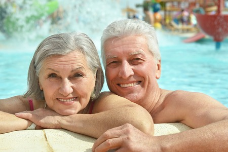 older women: Senior couple relaxing at pool at hotel resort Stock Photo