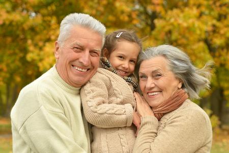 abuelos: Abuelos con su nieta en el parque del otoño Foto de archivo